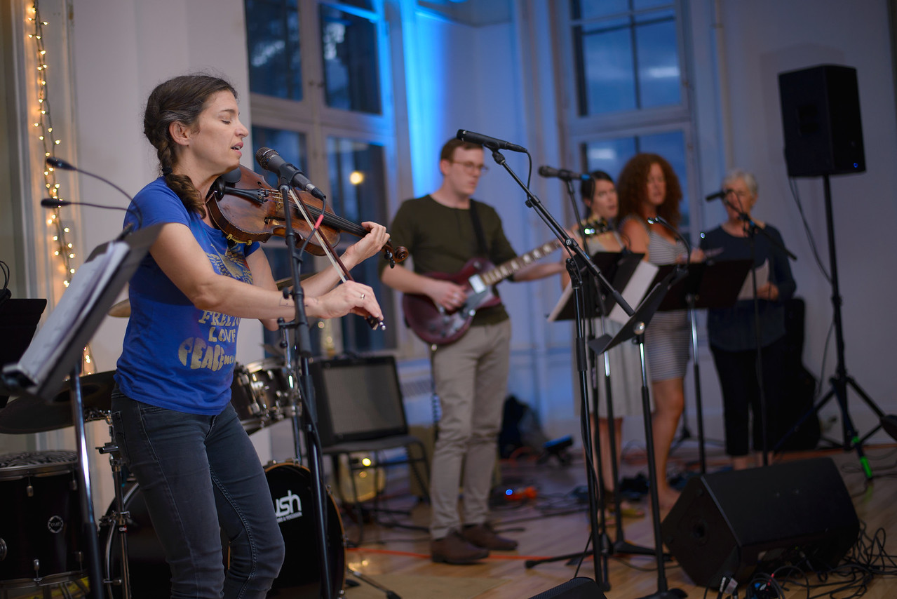 Image depicts VCFA faculty and students performing at the songwriters' showcase